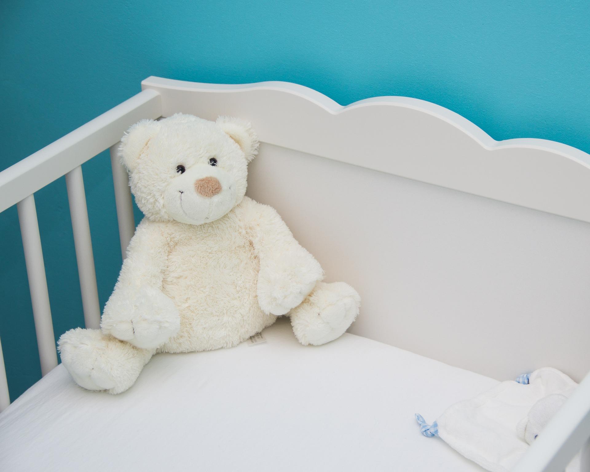 Teddybaer im Kinderbett